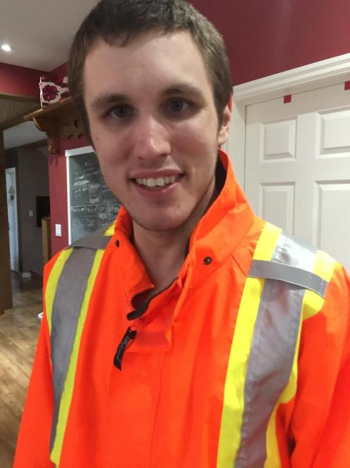 Kyle smiling.He is in an orange reflective work jacket.