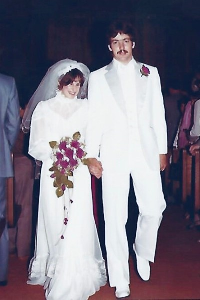 A bride and groom walking down the aisle of a church.