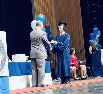 A young man receiving his diploma at his high school graduation.