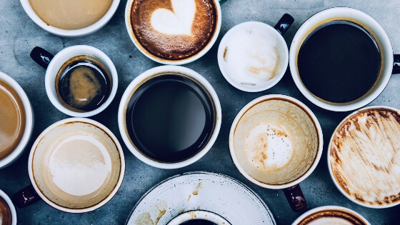a group of colorful mugs filled with coffee