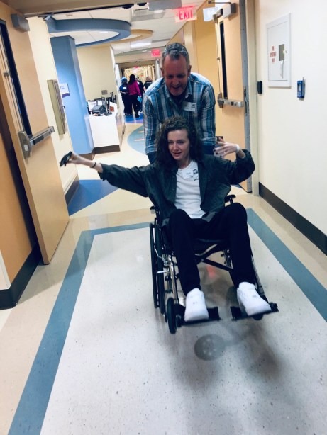 Jason pushing Gayle in a wheelchair through the hospital hallways