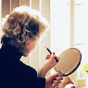 Gayle putting on her makeup.