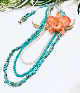turquoise necklace with coral coloured orchid