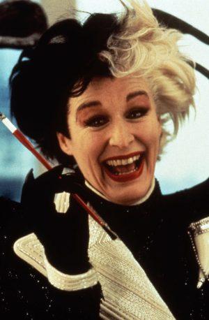 Primer plano de Glenn Close personificando a Cruella de Vil mientras sostiene un cigarrillo con boquilla. Tiene pelo bicolor.