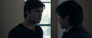 A young man talks to another in shadow.