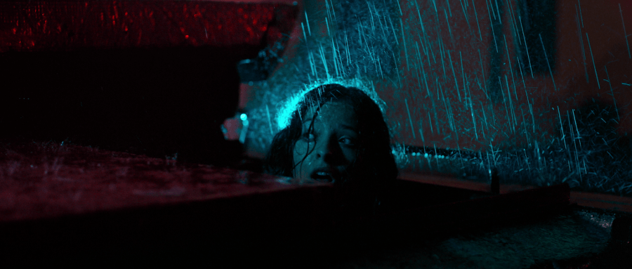 A young girl appears shocked as rain hits her head.
