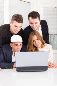 curious friends looking at laptop computer monitor together