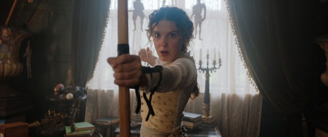 Enola Holmes apuntando un arco.