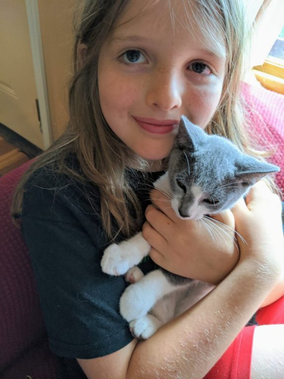 Silas holding Porco Rosso, a gray and white tuxedo cat