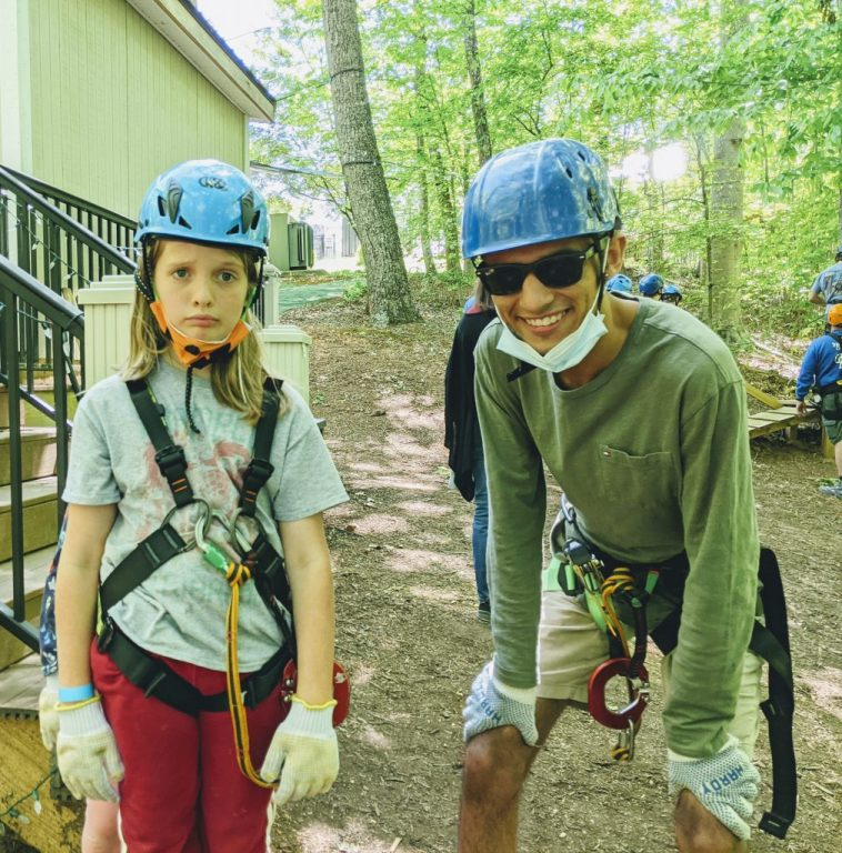 Carlos, grinning, with Silas, looking distressed, both wearing their high ropes gear--harnesses, gloves, helmets.