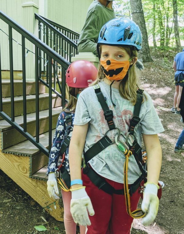 Silas, looking mildly distressed, wearing high ropes gear and a mask with a jack-o-lantern mask. Petra, wearing her gear, peeking out from behind him.