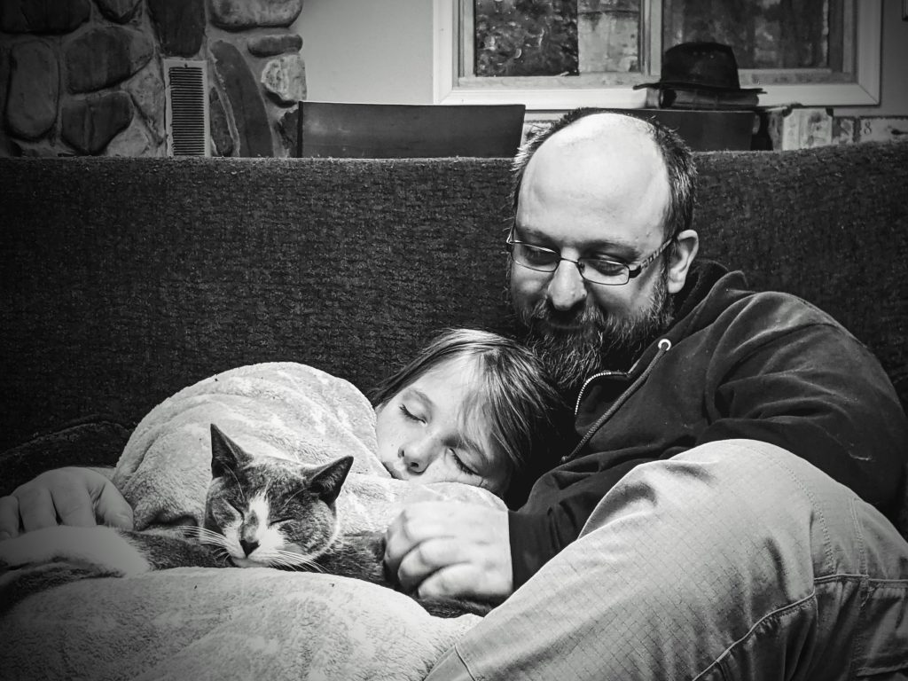 Silas cuddling with his dad and cat