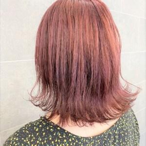 首が隠れる長さの薄紅色のヘアスタイル