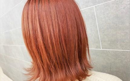 毛先を跳ねさせたオレンジカラーのミディアムヘアスタイル