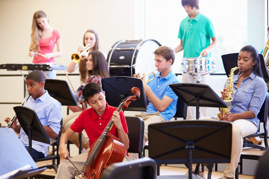 children in a music classroom playing school band instruments