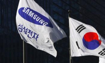 A Samsung flag (L) and South Korean national flag flutter outside the
