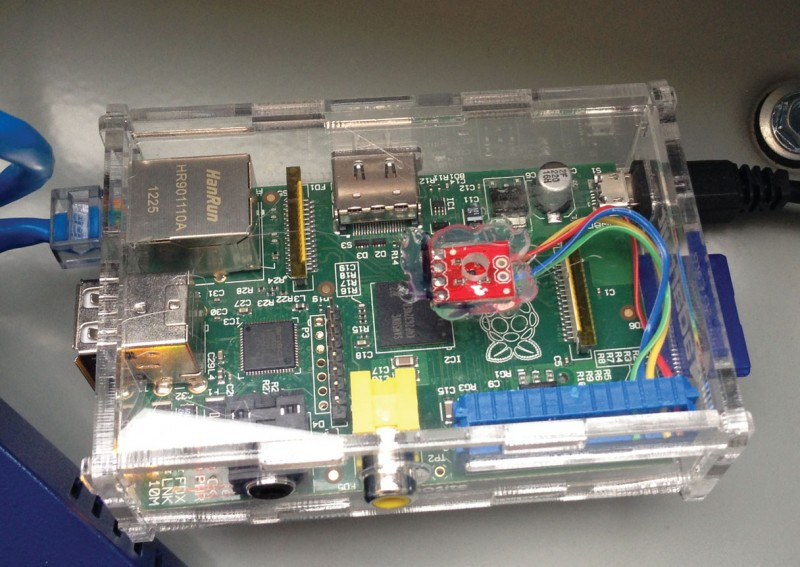 The Raspberry Pi's final installation is shown. The clear acrylic case can be seen along with the Texas Instruments TMP102 temperature sensor, which is glued below the air hole drilled into the case. We used a modified ribbon cable to connect the various TMP102 pins to the Raspberry Pi.