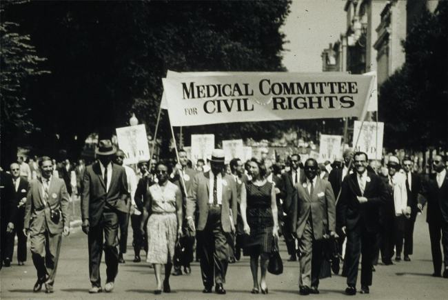 A group of people, black and white, men and women, in suits and dresses march under a banner reading Medical Committee for Civil Rights