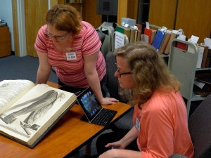 Two women look at an oversized book open to an anotomical illustration of a disected arm.