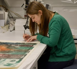 a woman uses a small tool to work on a corner of an art print.