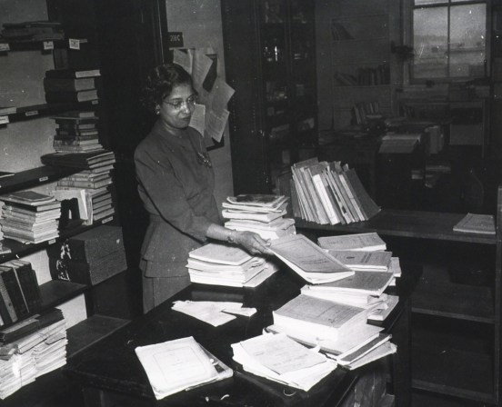Woman staff member sorting publications; material is on the table, a book truck, and shelves.