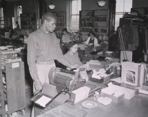 A man is standing at a duplicating machine. The woman sitting next to him is holding a group of catalog cards; two catalog card drawers are on her desk. Desks are equipped with manaul typewriters and bookshelves line the walls. Other staff members are working at their respective desks.