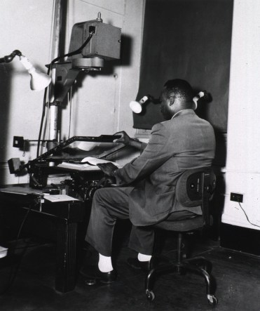 A man works with a at microfilm camera on a camera stand.