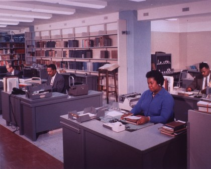 Mattie White, Mr. Richardson, and Mr. Green are sitting at their desks. Phillip Coleman is sitting behind Mattie White. Book shelves are behind Mr. Richardson and Mr. Green. A dictionary on a stand is in front of the shelves. There are typewriters by some of the desks, and an ashtray on Mattie White's desk.