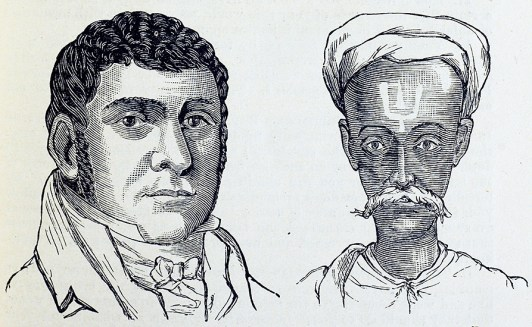 The heads of a round faced intense looking man and a thin man in a turban and mustache with a symbol painted on his forehead.