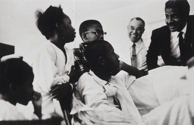 Four young patients look at Ossie Davis as he bends over to engage with them.