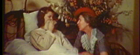 A young woman lies in bed, covering her mouth as she talks with an older woman seated at her bedside.