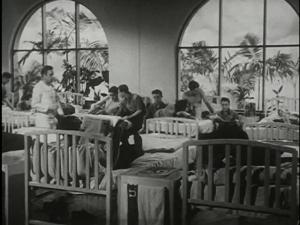 A scene of men lounging and socializing in a ward of a medical hospital.