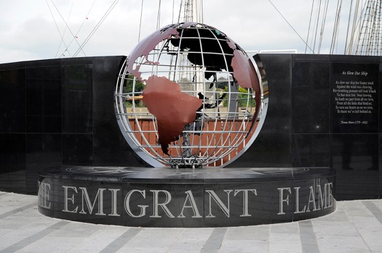 An open grid globe with sheetmental continents on a granite stage which says The Emmigrant Flame. Tall ship riggin visible in the background.