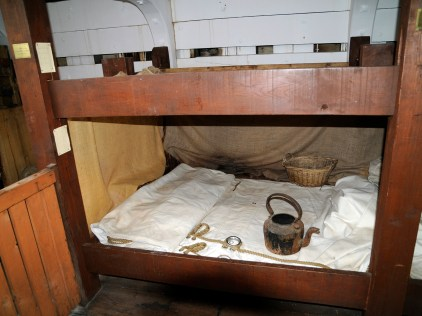 A short wooden bunk bed secured to the deck and hull, with sheets. A basket and metal tea pot and some ropes are on the lower bunk