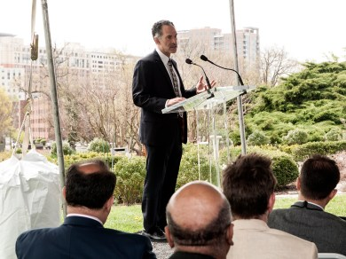 Dr. Lipman speaks at a podium on the lawn of the National Library of Medicine.