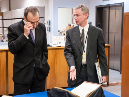 Micael North shows the Greek ambassador a rare book from the NLM collection.