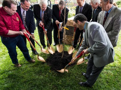 Eight dignitaries ceremonialy plant a new Hippocrates tree at the National Library of Medicine.