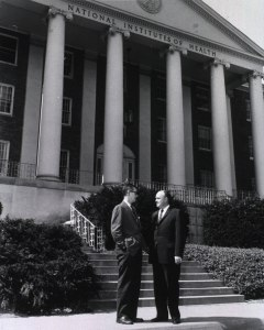 Two men in suits stand talking outside the columned porch of a building with a sign reading National Institutes of Health.