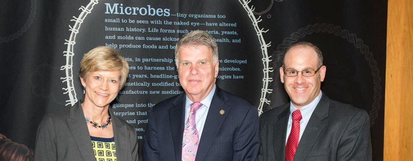 "Three people in business clothes pose in front of a banner that is headed ""Microbes"""