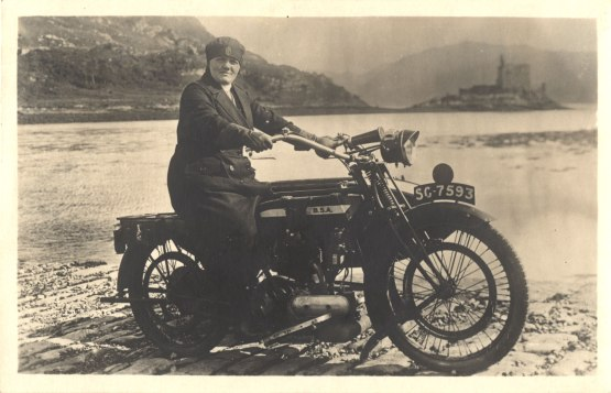 A woman in a dark overcoat and hat sits on a motercycle on a cobblestone road by a lake.