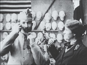 In front of a wall covered in masks a woman watches whil a man in uniform adjusts a mask.
