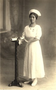 An Asian female nurse in white stands next to small podium with a diploma on it.