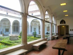 View into an open courtyard from inside a spanish influenced building with columns, tera cotta shingles, and arched windows.