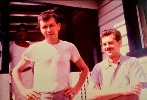 Two white men in short sleves stand outside a house.