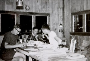 Three white men in shorts and tee shirts take notes and use a microscope in a rustic wood-paneled room.