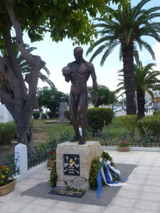 A bronze statue of a man, with musculature exposed, gazing at a skull held in his right hand.