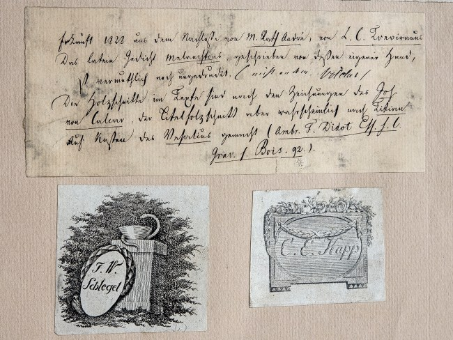 Three papers glued to the flyleaf page, one with handwritten text, two with printed images and names.