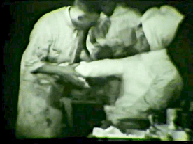 A doctor bandages up the left arm of a soldier who is seated.