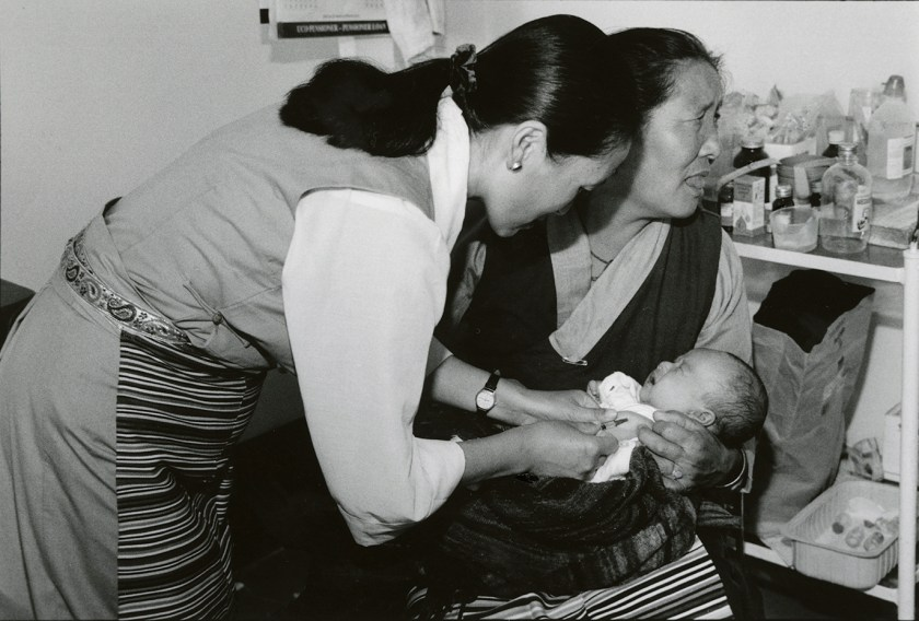 A woman gives a shot to an infant held in a woman's arms.