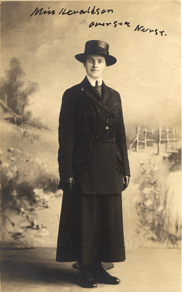 A postcard featuring a woman in a dark suit and hat posed against a drawing of an outdoor setting.